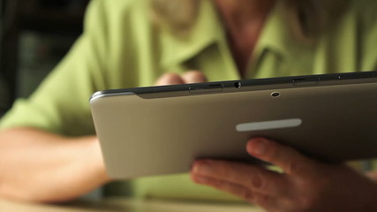 Close-up of a tablet computer in the hands of women aged
