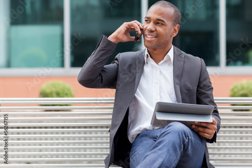 Afro American manager sitting on the bench and phoning
