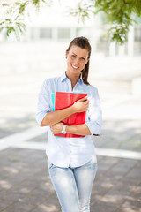 Portrait of female student with notebooks