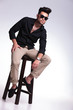 young man sitting on a stool
