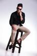 seated young man adjusting his shirt