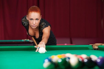 Sexy pool player. Beautiful young red hair woman playing pool