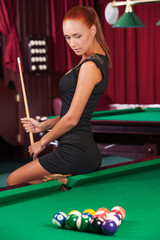 Sexy pool player. Beautiful young female pool player in black dr
