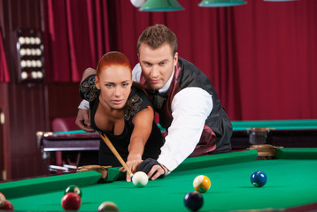 Playing pool. Confident man teaching beautiful young woman to pl