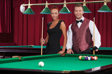 Playing pool. Beautiful young woman and young man standing close