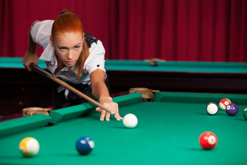 Pool player. Confident young red hair woman playing pool
