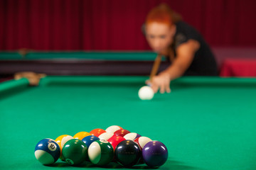 Playing pool. Confident young man aiming the billiard ball with