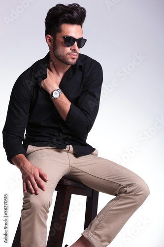 seated young man with hand tucked in shirt