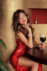 Rich slim beautiful girl resting sitting at the table holding vi