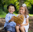 Two laughing kids holding wicker heart