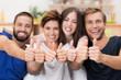 vier freunde lachen und zeigen daumen hoch