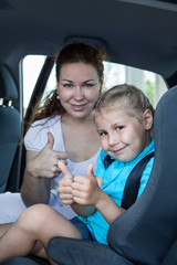 Mother and child with thumb up gesture in car safety seat