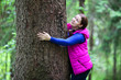 Joyful woman embracing pine stem in forest
