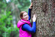 Smiling young woman touching stem of big pine in forest