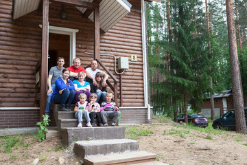 Large family with nine people sitting on house porch together