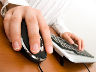 Businesswoman typing in the computer keyboard and using a mouse.