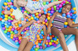 Multi Racial Girls Children Fun Playing in Colored Ball Pit
