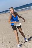 Healthy Senior Woman Playing Frisbee at Beach