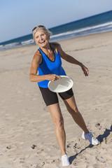 Healthy Senior Woman Playing Frisbee at Beach