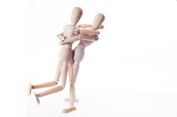 couple wooden manikins hugging
