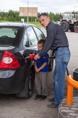 Senior grandfather with young boy refilling car at gas station