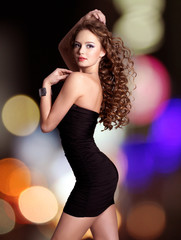 beautiful woman in black dress poses over night lights