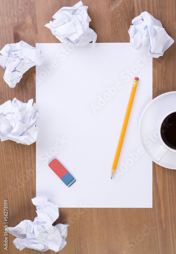 Crumpled paper balls and blank sheet of paper with pencil