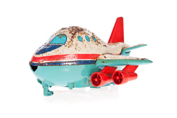 Old Jet plane rusty tin toy isolated on white
