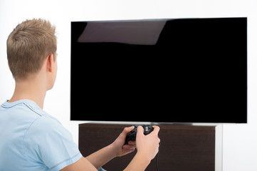 Gamer with joystick. Rear view of young gamer playing video game