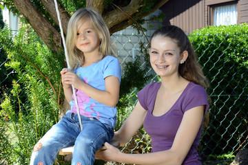 Teenager mit Kind auf Schaukel