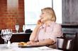 Seniorin im Restaurant mit Smartphone