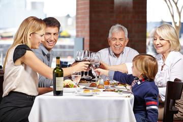 Familie im Restaurant prostet sich zu
