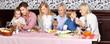 Familie beim Essen schaut auf Smartphone