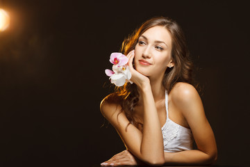Woman beauty portrait with orchids looking to the side