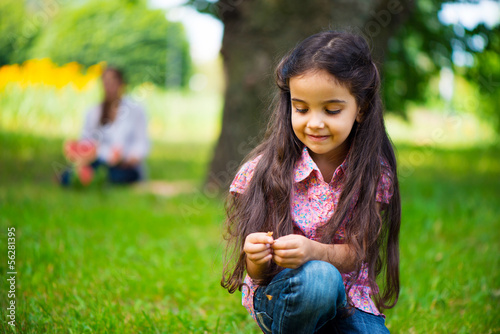 Cute hispanic girl in park with mother on background