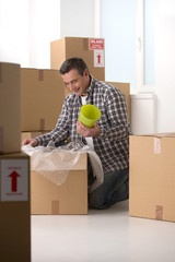 House moving. Cheerful middle-aged man packing the cardboard box