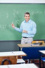 Male Teacher Teaching Mathematics On Board