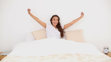 Young woman waking up and yawning in her bed