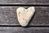 White stone heart on old wooden background.