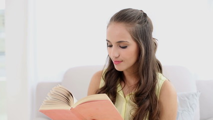 Young woman smiling and reading a book on the couch