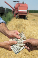 Farmer and buyer hands holding dollar banknote