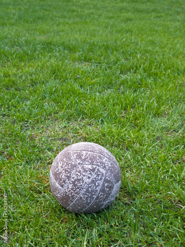 Old soccer ball in a green grass field