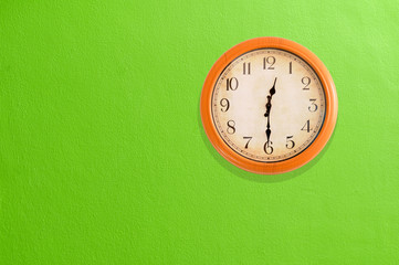 Clock showing 12:30 on a green wall