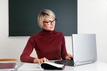 Lehrerin schreibt am Laptop