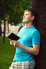 happy young man holding a book outdoors