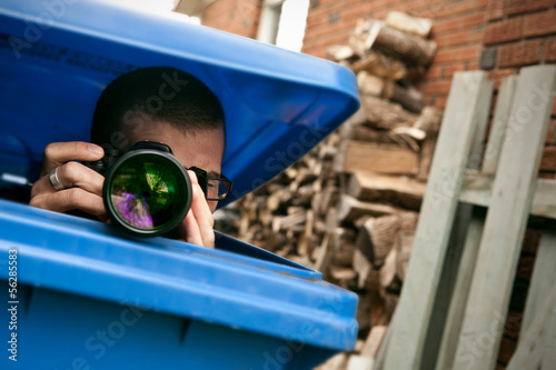 Paparazzi hiding in a blue garbage bin