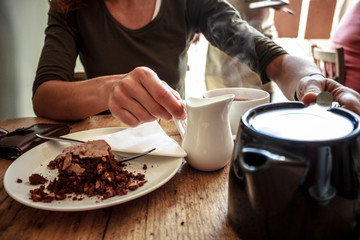 Young woman pouring herself a cup of tea and eating cake in cafe