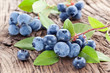 Blueberries with leaves on a wooden table.