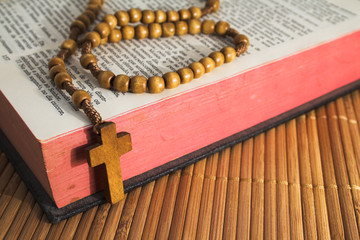 Open Bible with rosary on a straw table