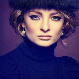 Portrait of beautiful blonde in a fur cap on a brown